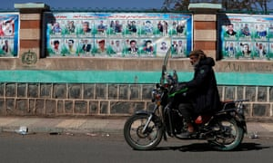 A motorcyclist drives past a wall with banners depicting portraits of late Houthi fighters/