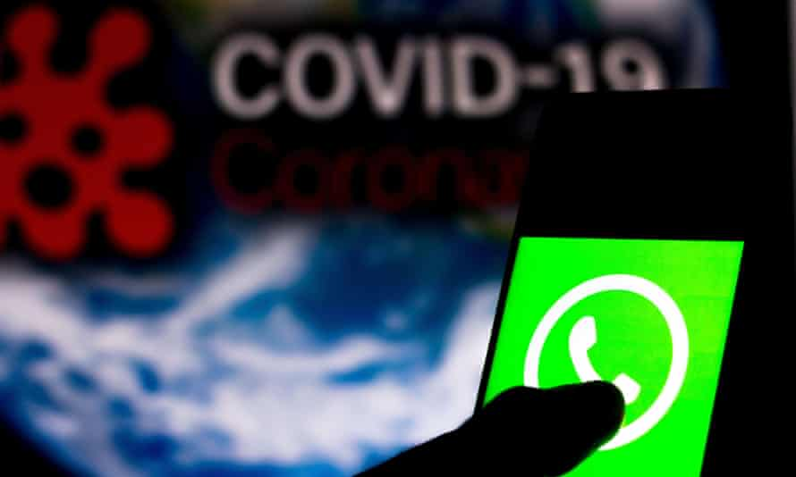 WhatsApp logo displayed on a smartphone with a computer model of the words 'Covid-19'  in the background