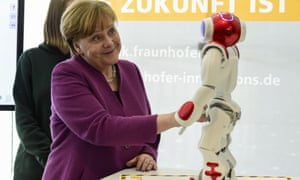 Angela Merkel with a robot. 'Good to see you again, Theresa.'