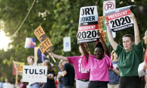 People hold up signs along First Avenue at an LGBTQ Presidential Forum in the Sinclair Auditorium on the Coe College campus in Cedar Rapids, Iowa, on Friday, 20 September.