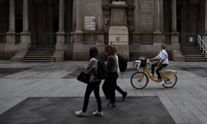 A woman rides a BikeMi bicycle on Via Mercanti in Milan. City authorities have encouraged cycling and riding e-scooters as a safer form of transport during the pandemic.