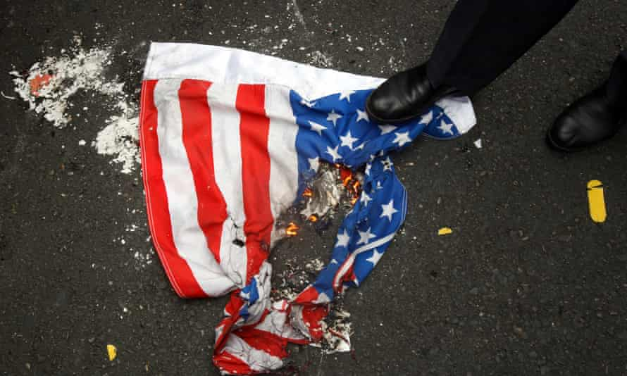 An Iranian steps over a burning US flag in Tehran. Washington's fractured relationship with Iran will be a key issue in Biden's nuclear policy.