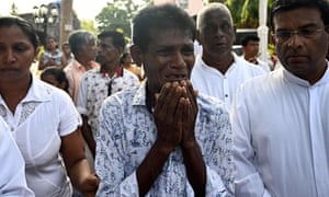 A man weeps as he walks behind the coffin of a bomb blast victim after a funeral service at St Sebastian's Church in Negombo.