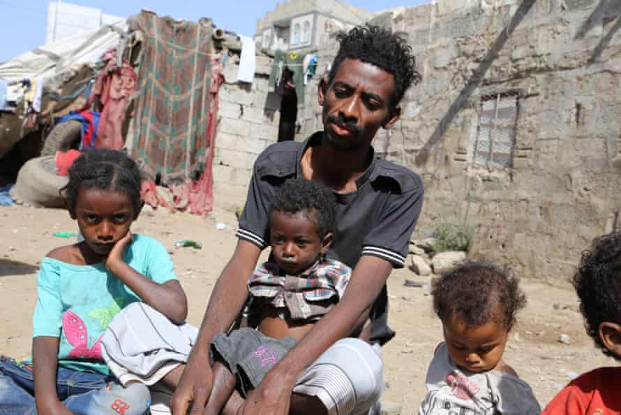 Juma'n Abdullah Hasan cradles his three-year-old son in Ibb city, Yemen