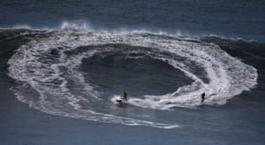 A surfer gets into position with the help of a jet-ski