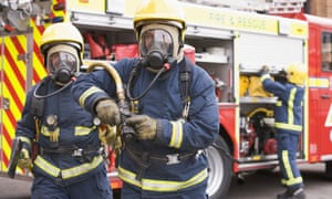 Firefighter carrying hose and firefighter holding axe