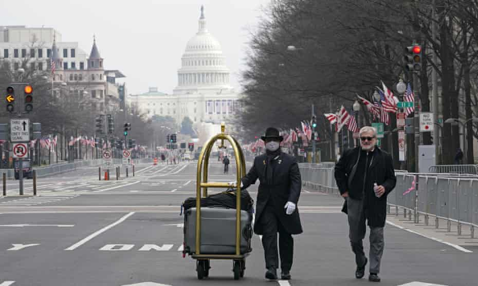 Danish Rozario, left, wheels a guest's baggage down Pennsylvania Avenue to the Trump Hotel in Washington on 15 January 2021. Joe Biden's inauguration five days later marked an ominous moment for the hotel's fortunes.