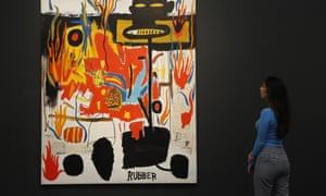 A Sotheby's employee looks at genuine Jean-Michel Basquiat painting, entitled Rubber during a sale in London.