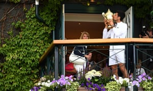 Novak Djokovic poses with the Wimbledon men's singles winner's trophy on the balcony of the club house.