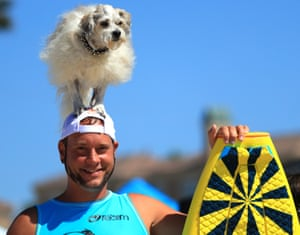 A dog stands on his owner's head