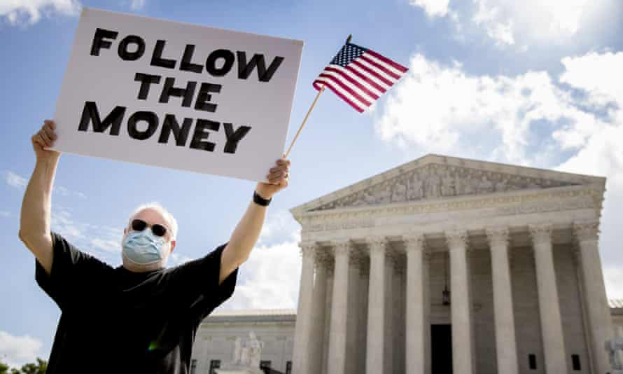 Bill Christeson holds up a sign that reads 'Follow the Money' outside the supreme court as it issued an initial ruling on the release of Donald Trump's tax returns last July.