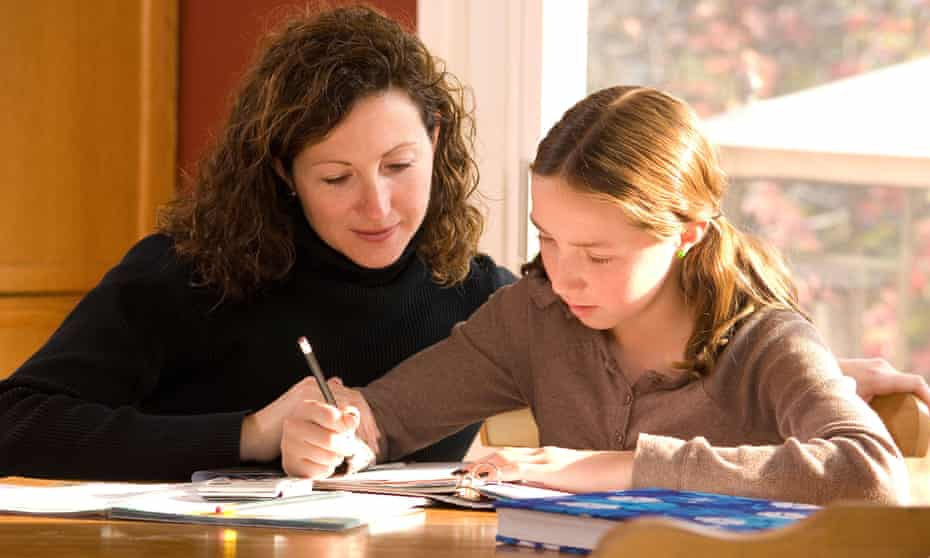 A mother helping her daughter with schoolwork at home. Picture posed by models.