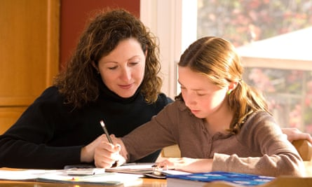 Mother helping her daughter with her home schooling homework in kitchen.
