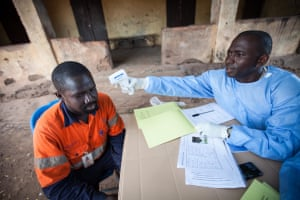 Souare Sekouba of the WHO vaccine trial team takes the temperature of a participant in the trial using an infrared, non-contact thermometer. Follow-up monitoring tracks the health of everyone involved in the trial, with participants checked three, nine, 21, 42, 63 and 84 days after vaccination