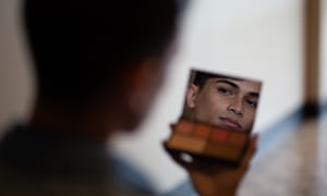Young man looks at himself in the mirror