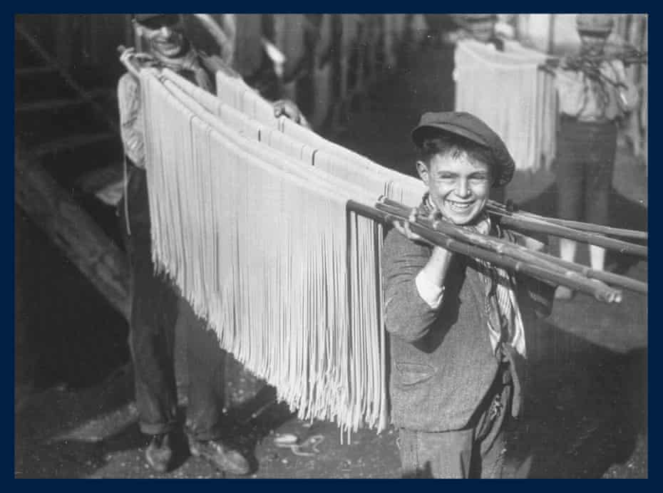 February 1929: A young boy carrying strings of pasta in a macaroni factory in Naples, Italy.