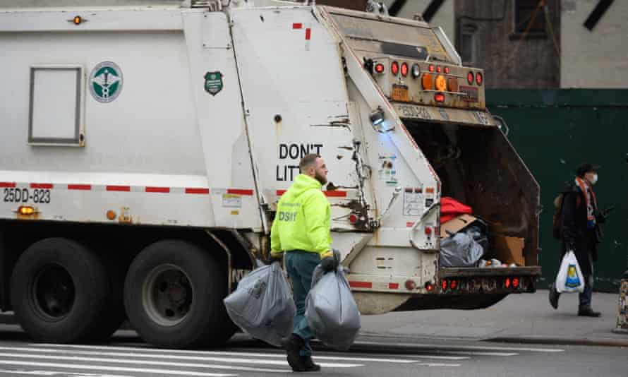 Sanitation workers collect trash along the streets in midtown Manhattan on 29 April.