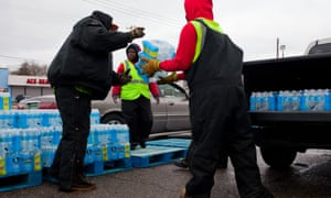 Workers load cars with cases of water in front of the closed bowling alley. Flint Michigan water supply crisis