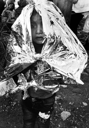 A young Afghan boy is wrapped in an emergency blanket on landing. As the weather changes many are now arriving with signs of hypothermia