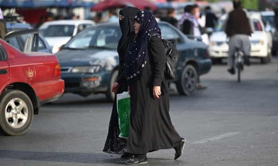 Women cross a street in Kabul.