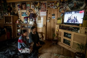 Lhakpa and his daughter, Tshering Yangchen, watch TV in their house in Phobjikha Valley