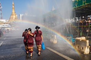 "Yangon, MyanmarWomen walk under a rainbow during the Buddhist New Year, known locally as ""Thingyan"""