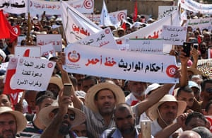 Hundreds of Tunisians hold pro-conservative signs during a protest against proposed reforms opposed by conservative Muslims, which include equal inheritance rights for women and decriminalising homosexuality, in August 2018, Tunis