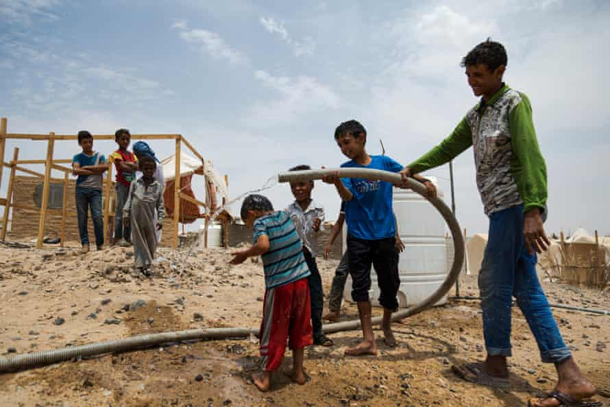 Children playing with water during a water distribution, in the al-Jafinah IDP camp