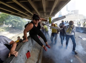 Demonstrators try to get away from the tear gas
