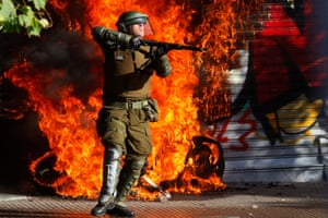 A police officer raises his weapon as a fire burns behind him