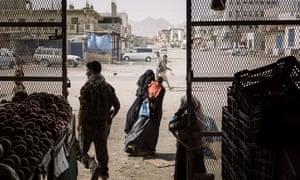 A woman begs outside a grocery store in the town of Azzan, Yemen