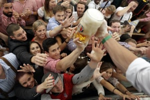 Visitors try and grab the free beer during the opening ceremony