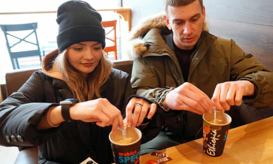 Alexandr Kudlay and Viktoria Pustovitova drink coffee in a cafe in Kharkiv