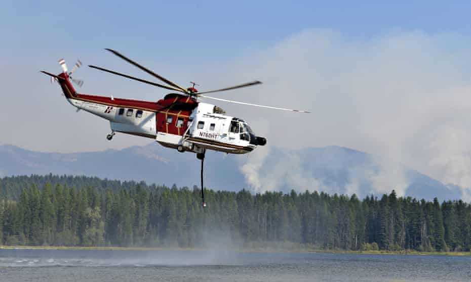 A helicopter fills its water tank as it readies to battle a wildfire. Across Montana, wind is fanning numerous fires in the drought-addled state.