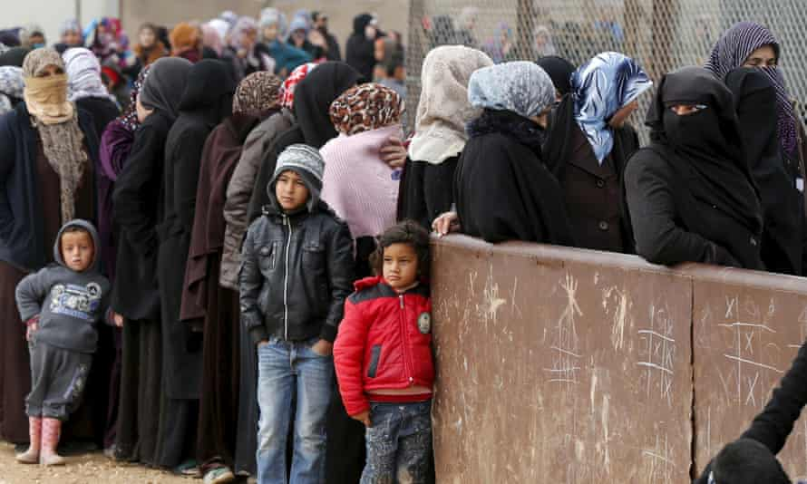 Syrian refugees stand in line as they wait for aid packages at a refugee camp in the Jordanian city of Mafraq, near the border with Syria.