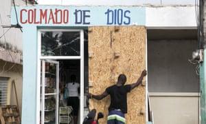 A man covers a bodega's windows in Las Terrenas.