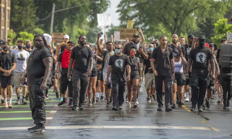 Protesters march towards the barricade of the George Floyd Memorial in Minneapolis, Minnesota after marching 8 miles over 5 hours in 95F (35C) heat.