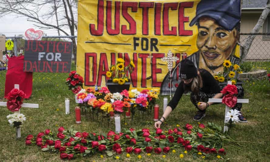 A person decorates a memorial for Daunte Wright with flowers and dandelions earlier this month in Brooklyn Center, Minnesota.