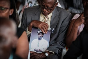 Vianney Rusanganwa, 61, holds a portrait of his late wife Liberatha Mukangira who died aged 31, during the mass funeral to bury 81 coffins containing newly discovered remains of 84,437 victims of the 1994 genocide