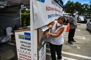 Poll workers help a voter put their mail-in ballot in an official Miami-Dade County drive-thru ballot drop box in Miami, Florida on 18 August.