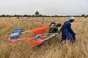 Villagers collect rations parachuted from a plane onto a drop zone at a village in Ayod county, South Sudan