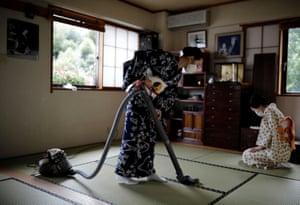Koiku and Maki, who are geisha, clean Ikuko's living room before they have lunch together at Ikuko's home