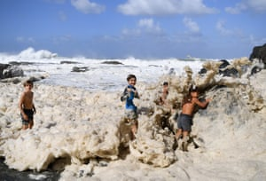 Children play in sea foam generated by cyclone Oma, Snapper Rocks, Australia