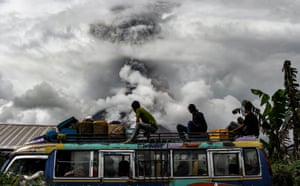 Karo, IndonesiaBus passengers watch as mount Sinabung spews thick smoke. The mountain roared back to life in 2010 for the first time in 400 years. After another period of inactivity it erupted once more in 2013 and has remained highly active since.