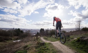 A mountain biker takes flight on a track outside of Sheffield city centre. The city skyline is in the background of this dynamic extreme sports shot.