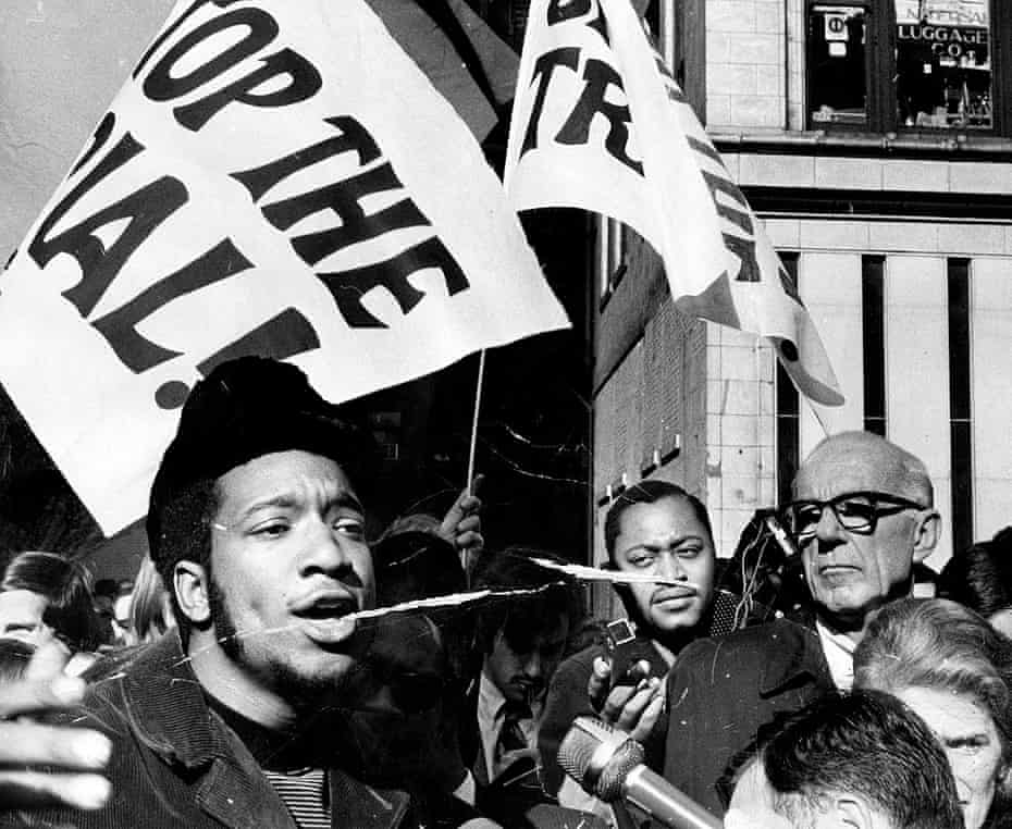 Fred Hampton, left, and Dr. Benjamin Spock, right, attend a rally against the trial of eight people accused of conspiracy to start a riot at the Democratic National Convention.