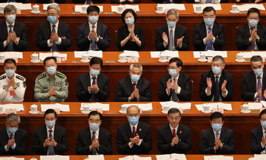 Attendees of the Second Plenary Session of the National People's Congress clap their hands during a speech on May 25