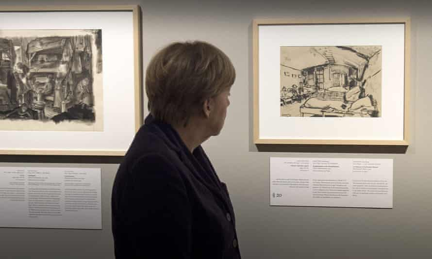 Chancellor Angela Merkel looks at an image from the Theresienstadt concentration camp during a preview of Art from the Holocaust in Berlin.
