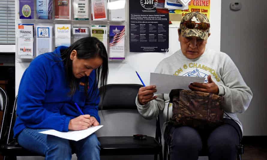 Members of the Standing Rock Sioux Tribe in Fort Yates fill out forms to receive new tribal IDs with street addresses.