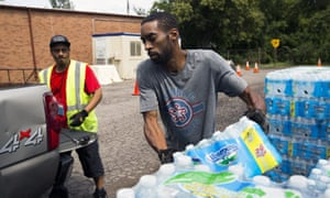 People distribute bottled water in Flint. Water lead levels are 'back to normal levels for a city with old lead pipes', says an expert.
